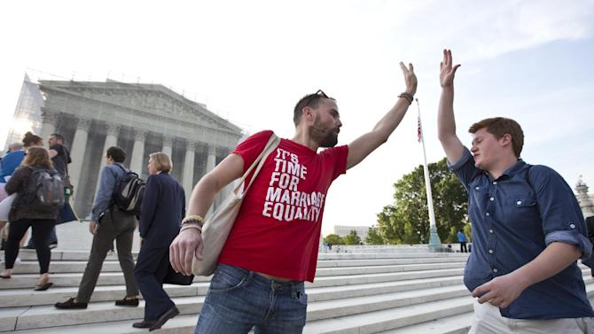Gay rights activist Bryce Romero, who works for the Human Rights Campaign, offers an enthusiastic high-five to visitors getting in line to enter the Supreme Court on a day when justices are expected to hand down major rulings on two gay marriage cases that could impact same-sex couples across the country, in Washington, Wednesday, June 26, 2013. (AP Photo/J. Scott Applewhite)
