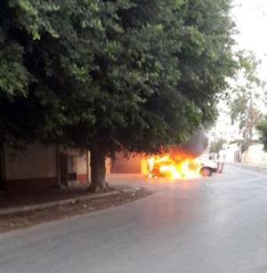 Burning car is seen in front of the Russian embassy, as it came under attack in Tripoli