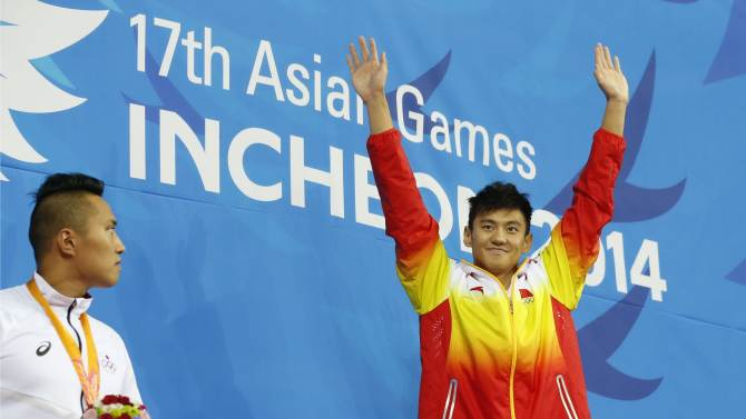 Ning raises his hands on the podium after winning the men's 50m freestyle final swimming competition during the 17th Asian Games in Incheon