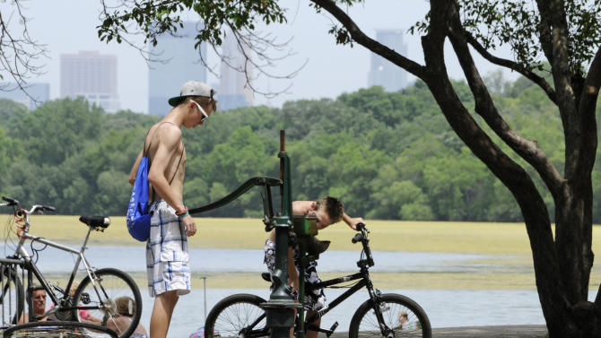 The skyline rises through haze as one boy pumps water for another to drink from an old-fashioned water pump along Lake Harriet Friday, July 6, 2012 in Minneapolis where temperatures reached into the upper 90's for another day during the heat wave.  The National Weather Service said the record-breaking heat that has baked the nation's midsection for several days was slowly moving into the mid-Atlantic states and Northeast. Excessive-heat warnings remained in place Friday for all of Iowa, Indiana and Illinois as well as much of Wisconsin, Michigan, Missouri, Ohio and Kentucky. (AP Photo/Jim Mone)