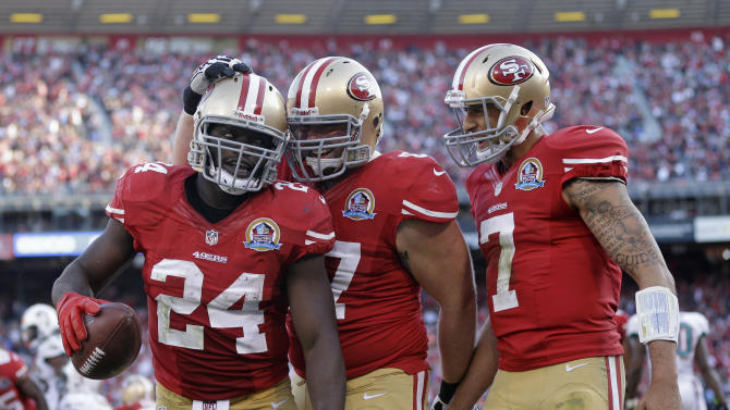 San Francisco 49ers running back Anthony Dixon, left, is greeted by tackle Daniel Kilgore, center, and quarterback Colin Kaepernick after scoring a touchdown during the fourth quarter of an NFL football game in San Francisco, Sunday, Dec. 9, 2012. (AP Photo/Marcio Jose Sanchez)