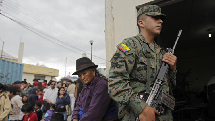 A woman waits in line to vote next to a soldier  at a polling station in Quito, Ecuador, Sunday, Feb.17, 2013. Ecuadoreans  elect president,  vice-president and National Assembly members Sunday with President Rafael Correa highly favored to win a second re-election.(AP Photo/Dolores Ochoa)