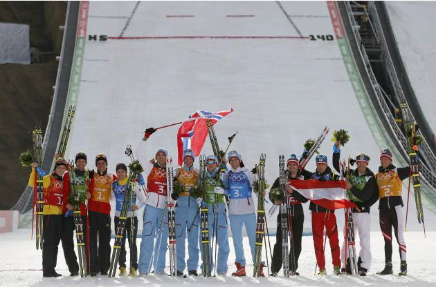 Germany's second placed team members, Norway's winning team members and Austria's third placed team members celebrate after the flower ceremony for the of the Nordic Combined team Gunderse