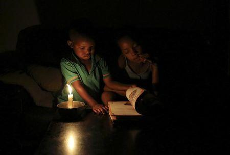 Bhungane looks on as her studies are interrupted by her cousin as she studies using candle light during load shedding in Soweto