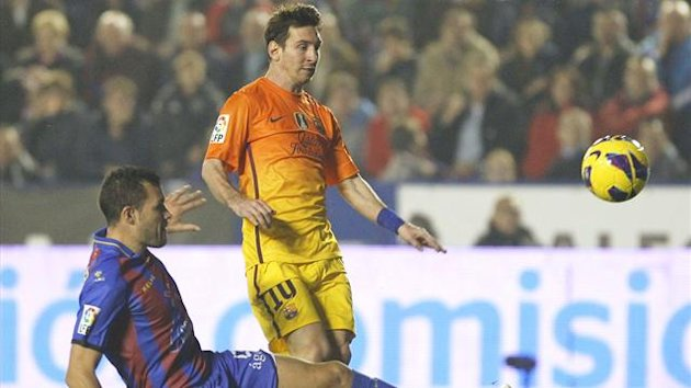 Barcelona's Lionel Messi (R) shoots to score past Levante's David Navarro during their match the Ciudad de Valencia stadium (Reuters)