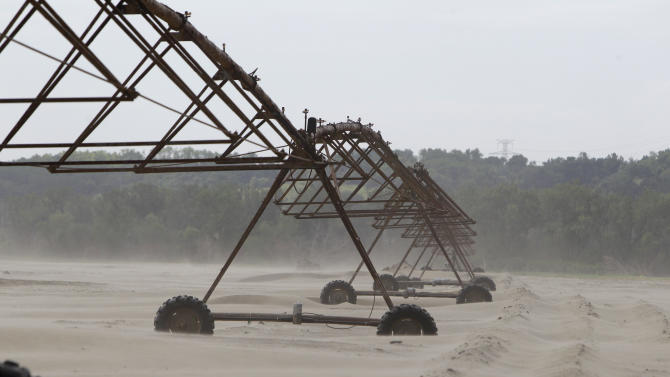 This May 22, 2012, photo shows irrigation equipment surrounded by sand on the Mason Hansen farm in Missouri Valley, Iowa. Hundreds of farmers in Iowa and Nebraska are still struggling to remove sand and fill holes gouged by the Missouri River, which swelled last summer with rain and snowmelt and overflowed onto thousands of acres of farmland. (AP Photo/Charlie Neibergall)
