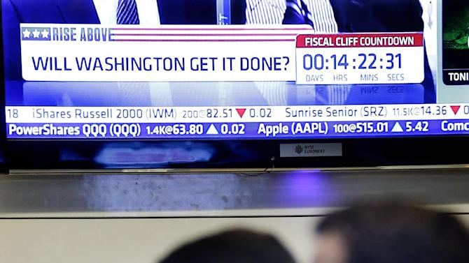 "A television news show talks about the fiscal cliff while traders work on the floor at the New York Stock Exchange in New York, Monday, Dec. 31, 2012. The stock market struggled for direction Monday morning after five days of losses, with the ""fiscal cliff"" just hours away and lawmakers yet to reach a solution. (AP Photo/Seth Wenig)"