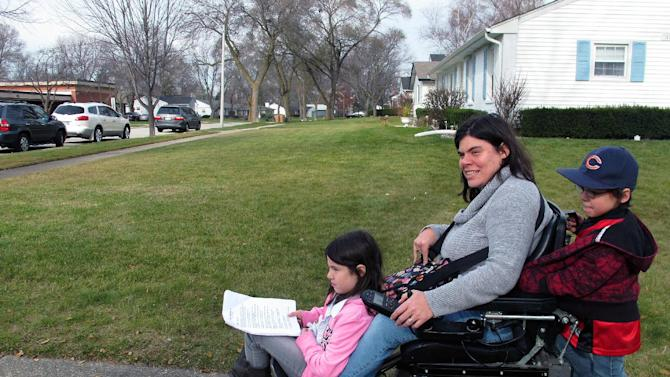"In this Nov. 19, 2012 photo, twins Abigail and Noah Thomas, 8, ride on the motorized wheelchair of their mother, Jenn Thomas, on their way to a school book fair in Arlington Heights, Ill. Thomas, a 36-year-old mom who has cerebral palsy, says her twins occasionally complain about having to do a few extra chores around the house to help her. Abigail nods and smiles upon hearing this, but says for the most part, their lives are ""kind of normal."" For her, having a mom with a disability is just how it is, she said. (AP Photo/Martha Irvine)"