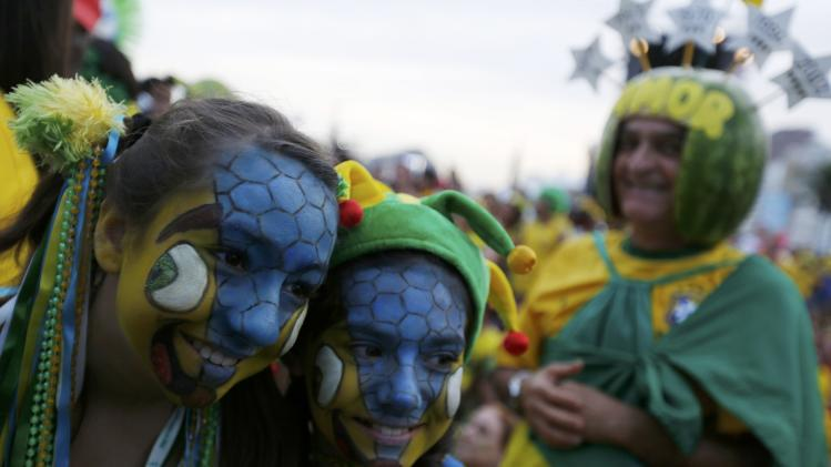 Brazilian fans pose for a photo as they watch the match between Brazil and Cameroon which was broadcast on a large screen at Copacabana beach in Rio de Janeiro