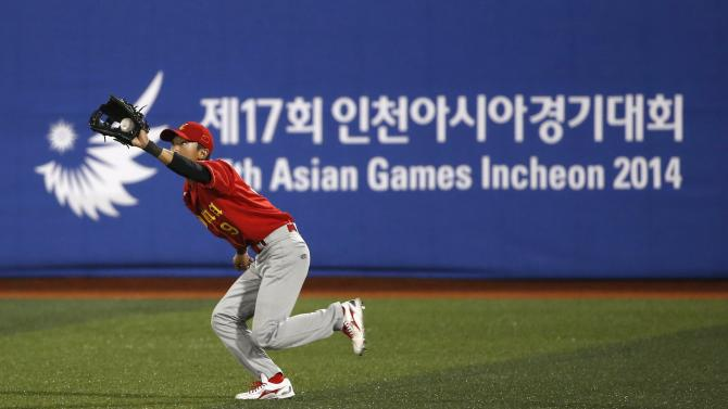 China's right fielder Zhai catches a fly out from Japan's Kuramoto in the first inning during a preliminary round baseball game at the Mokdong Baseball Stadium in Seoul, during the 17th Asian Games