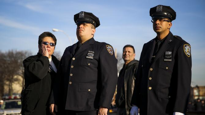 Members of the NYPD watch a tribute video for the funeral of slain NYPD officer Ramos near Christ Tabernacle Church in the Queens borough of New York