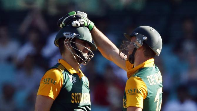 South Africa's captain AB de Villiers congratulates team mate Rilee Rossouw after he made his fifty during their Cricket World Cup match against the West Indies at the SCG