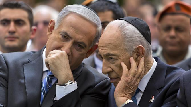 Israeli Prime Minister Benjamin Netanyahu, left, speaks with Israeli President Shimon Peres during the Remembrance Day ceremony in the Mount Herzl Military Cemetery in Jerusalem, Israel, Monday, April 15, 2013. The sad atmosphere ends sharply at sundown when in jarring contrast, Israelis joyfully take to the streets for independence day celebrations with dancing, fireworks and parties. (AP Photo/Jim Hollander, Pool)