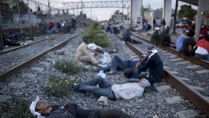 In this May 17, 2012 photo, migrants, mostly from Honduras, rest on railroad tracks as they wait for a train headed north, in Lecheria, on the outskirts of Mexico City. While the number of Mexicans heading to the U.S. has dropped dramatically, a surge of Central American migrants is making the 1,000-mile northbound journey this year, fueled in large part by the rising violence brought by the spread of Mexican drug cartels. (AP Photo/Alexandre Meneghini)