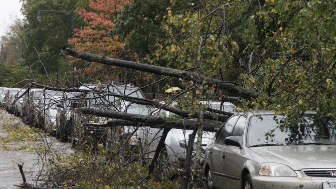 Trees lie fallen across parked cars in the Brooklyn borough of New York the morning after superstorm Sandy made landfall, Tuesday, Oct. 30, 2012. A record storm surge that was higher than predicted along with high winds damaged the electrical system and plunged millions of people into darkness. Utilities say it could be up to a week before power is fully restored. (AP Photo/Mark Lennihan)