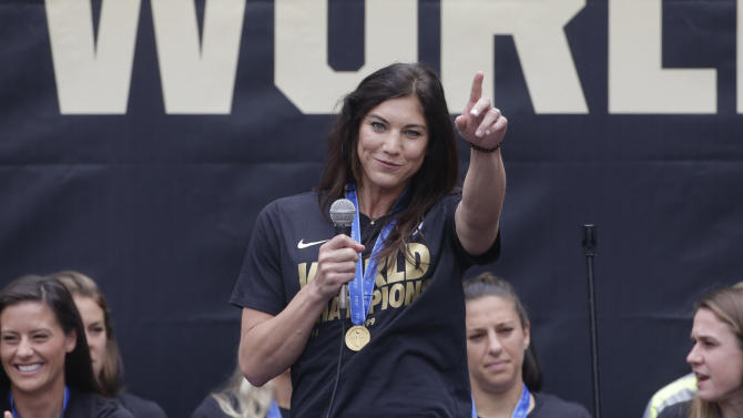 U.S. women's soccer team goalie Hope Solo, center, points to the crowd while celebrating the team's World Cup championship during a public celebration, Tuesday, July 7, 2015, in Los Angeles. This was the first U.S. stop for the team since beating Japan in the Women's World Cup final Sunday in Canada. (AP Photo/Jae C. Hong)