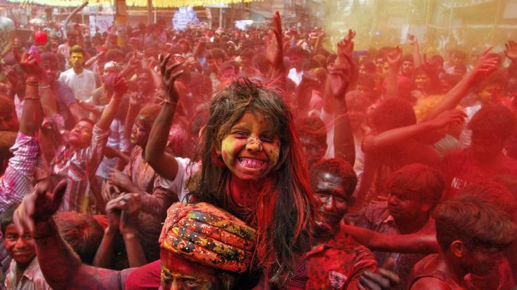 A girl sits on her father's shoulders cheers as she and others daubed in colours dance while celebrating Holi in Guwahati