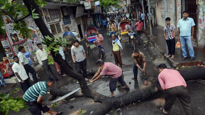 Bangladeshi workers cut a tree left by protesters to block a road during a protest in Savar near Dhaka, Bangladesh, Monday, May 6, 2013. At least 15 people died in clashes in Bangladesh Monday between police and Islamic hardliners demanding that Bangladesh implement an anti-blasphemy law, police said. (AP Photo/Ismail Ferdous)