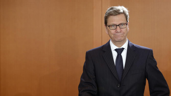 German Foreign Minister Guido Westerwelle stands behind his chair at the beginning of the weekly cabinet meeting at the chancellery in Berlin, Germany, Wednesday, March 6, 2013. (AP Photo/Michael Sohn)