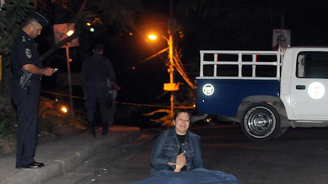 In this Oct. 30, 2012 photo, Karla Escoto grieves over the body of her husband, police officer Henry Amador Roque after he was killed by assailants who robbed his car in the capital city of Tegucigalpa, Honduras. The political turmoil is but the latest trouble bedeviling Honduras. Even in the best of times, president Porfirio Lobo's government, police and military exercise control over only about two-thirds of the country. (AP Photo/Fernando Antonio)