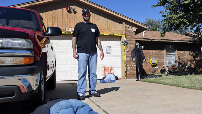 Johnnie Mullins poses with his controversial Halloween display featuring headless dummies dressed in his work clothes at his home in Mustang, Okla, Thursday, Oct. 17, 2013. In the display, one dummy lies under a truck with blood splattered on the driveway, foreground, and another along the blood-stained garage door. Mullins' wife, Jennifer, said she got the idea for the macabre scene from the social media site Pinterest. (AP Photo/Sue Ogrocki)