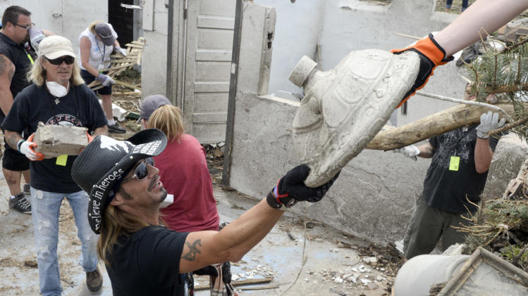 In this photo taken on Monday, June 23, 2014, rock star Bret Michaels hands an item up to another volunteer from the basement of a Pilger, Neb., home destroyed in last week's tornado. Michaels and his band and crew stopped in Pilger on Monday to see the devastation and do some volunteer cleanup work. (AP Photo/The Norfolk Daily News, Darin Epperly)