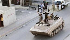 Militant Islamist fighters hold the flag of Islamic State (IS) while taking part in a military parade along the streets of northern Raqqa province in this June 30, 2014 file photo.