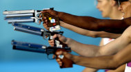 Competitors take aim in the combination running and shooting stage of the men's modern pentathlon at the 2012 Summer Olympics, Saturday, Aug. 11, 2012, in London. (AP Photo/David Goldman)