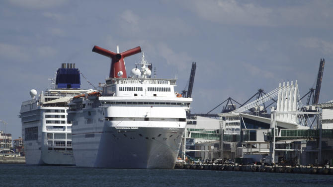 This Sept. 16, 2011 photo, shows the Carnival Imagination cruise liner, foreground, docked in the Port of Miami awaiting departure for a three day cruise to Nassau. Carnival Corp.'s third-quarter net income rose 3 percent as the cruise operator was helped by lower costs and strong ticket prices during its peak summer season. (AP Photo/J Pat Carter)