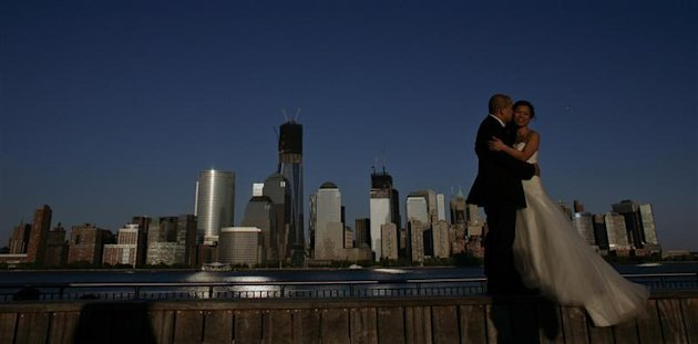 A couple, posing for their pre-wedding photographs, are back-dropped by the One World Trade Center and Manhattan skyline as seen from New Jersey April 29, 2012.