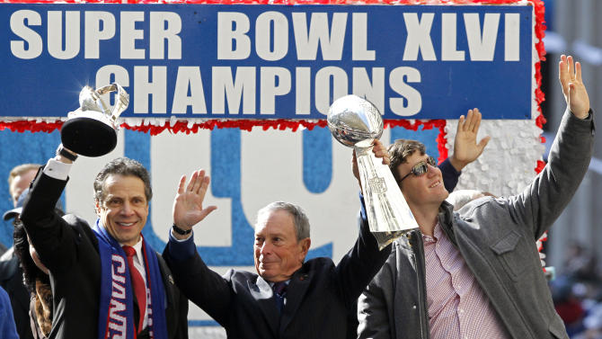 New York Gov. Andrew Cuomo, left, holds the Halas Trophy, while New York Mayor Michael Bloomberg, center, holds the Vince Lombardi Trophy as New York Giants quarterback Eli Manning, right, waves to the crowd during a ticker-tape parade celebrating the team's NFL football Super Bowl XLVI championship, Tuesday, Feb. 7, 2012, in New York. The Giants beat the New England Patriots 21-17 on Sunday, Feb. 5, in Indianapolis. (AP Photo/Julio Cortez)