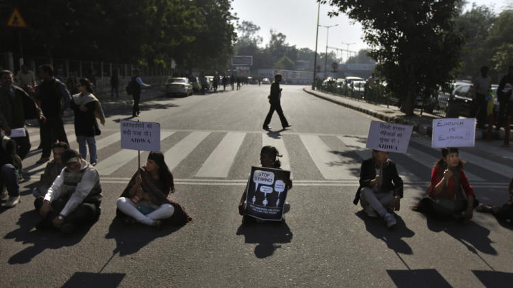 "Indian protesters hold placards as they block a major traffic intersection during a protest in New Delhi, India, Wednesday, Dec. 19, 2012. The hours-long gang-rape and near fatal beating of a 23-year-old student on a bus in New Delhi triggered outrage and anger across the country Wednesday as Indians demanded action from authorities who have long ignored persistent violence and harassment against women. The placards read as, left, ""Give harsh punishment to the culprits,"" second from right, ""Delhi government: Protect women.""  (AP Photo/Altaf Qadri)"