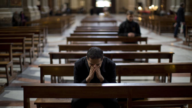 """A priest prays inside the Church of Saint Ignatius, dedicated to Ignatius of Loyola, the founder of the Jesuit order, in Rome, Thursday, March 14, 2013. Pope have punished Jesuits theologians for being too progressive in preaching and teaching. The last pontiff, Benedict, politely but firmly sent a letter to the Jesuit's leader inviting members to pledge """"total adhesion"""" to Catholic doctrine, including on divorce, homosexuality and liberation theology. Now the pope is a Jesuit, the first ever from the missionary order's well-educated and savvy ranks in its nearly 500-year-long history, and Francis just heard the church cardinals pledge allegiance to him. (AP Photo/Emilio Morenatti)"""