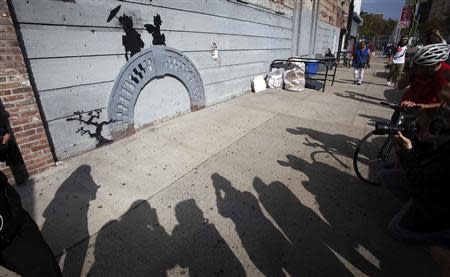 People take photos of a new art piece by British graffiti artist Banksy in the Brooklyn borough of New York