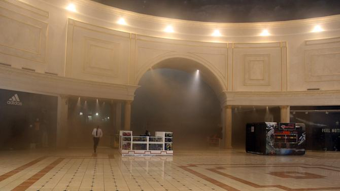 A man runs through smoke in the Villaggio Mall, in Doha's west end, as a fire took hold of the upscale mall in the Qatari capital of Doha Monday May 28, 2012. Qatar's Interior Ministry said 13 children were among 19 people killed in a fire that broke out at one of the Gulf state's fanciest shopping mall on Monday. The Villaggio opened in 2006 and is one of Qatar's most popular shopping and amusement destinations. It includes an ice skating rink and indoor Venice-style gondola rides. (AP Photo/Osama Faisal)