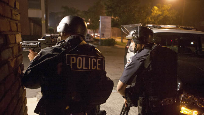 Police respond in Riverside, Calif., early Thursday morning, Feb. 7, 2013, after one officer was killed and another critically wounded in a shoot out with a murder suspect.  Police were searching for a former Los Angeles police officer sought for two weekend killings , and who threatened to kill police.  There were two separate overnight shootings about 60 miles east of Los Angeles in Riverside County that investigators believe involved former LA police officer Christopher Dorner, who's also the main suspect in the weekend killing of a couple whose bodies were found in Irvine. He was fired in 2008 for making false statements. (AP Photo/Kevin Warn)