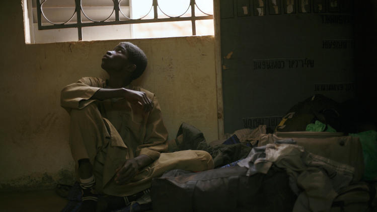 Adama Drabo, 16, sits in the police station in Sevare, some 620 kilometers (385 miles) north of Mali's capital Bamako Friday, Jan. 25, 2013. Drabo,  who said he was captured travelling without papers by Malian troops and eventually handed over to Gendarmes in Sevare, was arrested on suspicion of working for Islamic militant group MUJAO and caught trying to flee south, Police said. A farmer's son from Niono, he  admitted to having worked in the kitchens of a jihadist training base in Douentza for the past month. Drabo said his only motivation in joining the Islamic militant group had been to earn a wage, having struggled to find work at home, and that he was one of the youngest recruits on the base. (AP Photo/Jerome Delay)