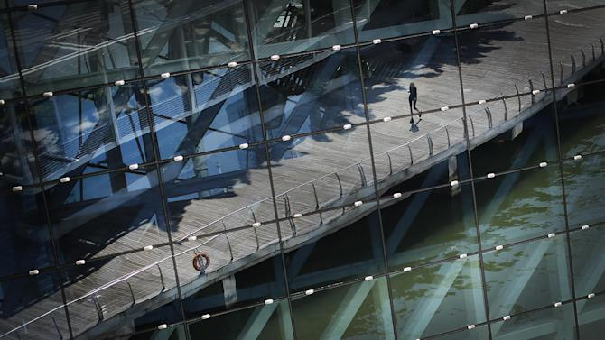A tourist is seen in a reflection off the facade of a shopping mall at the Marina Bay Sands, which is a popular tourist spot with hotels, shopping, and casinos, Tuesday, April 21, 2015, in Singapore. The city-state's government announced earlier in the year, new plans for its global marketing campaign to tap on the country's year-long 50th birthday celebration, as part of its continued effort to boost tourism numbers in 2015, after the country went through a challenging season in 2014. (AP Photo/Wong Maye-E)