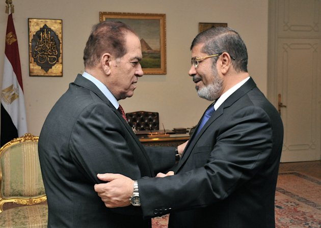 In this photo released by Middle East News Agency, the Egyptian official news agency, caretaker Prime Minister Kamal el-Ganzouri, left, shakes hands with newly elected President Mohammed Morsi in Cairo, Egypt, Monday, June 25, 2012. Morsi met with the military-backed Prime Minister el-Ganzouri, who resigned Monday and was asked to head a caretaker government until Morsi nominates a new one. (AP Photo/Middle East News Agency, HO)
