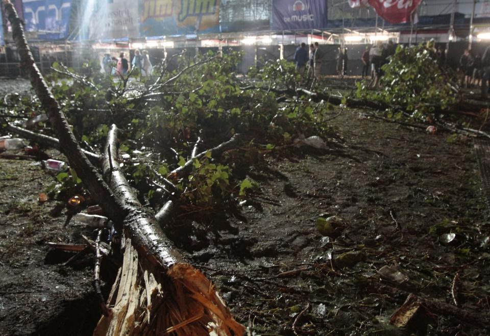 A tree has fallen after a storm swept through an open air music festival near Hasselt, about 50 miles (80 kilometers) east of Brussels, Belgium, Thursday, Aug. 18, 2011. The storm killed at least three people and injured over 70 others, an official said.  (AP Photo/Yves Logghe)