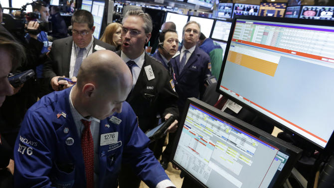 FILE - In this Monday, March 25, 2013, file photo, Specialist Mario Picone, left, works with traders at his post on the floor of the New York Stock Exchange. Renewed jitters about Europe's debt crisis sent world stock markets lower Thursday March 28, 2013. (AP Photo/Richard Drew, File)