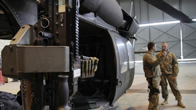 In this Saturday, Jan. 28, 2012 photo, U.S. military personnel stand near a Black Hawk helicopter inside a hangar at the U.S. Bagram air field north of Kabul, Afghanistan. About 20 U.S. lawmakers have written to military officials inquiring about a Sept. 18, 2011 incident, when it took a medevac unit 59 minutes to get U.S. Army Spec. Chazray Clark, a 24-year-old combat engineer from Detroit, to a hospital in southern Afghanistan after receiving a call that a roadside bombing severed three of his limbs. Clark did not survive. The incident has revived a debate over whether medevac helicopters should have their own guns, as Black Hawks and other helicopters do. (AP Photo/Musadeq Sadeq)