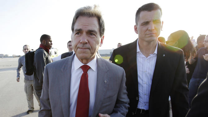Alabama head coach Nick Saban, foreground, heads to the team bus after speaking to the media upon arrival at Miami International Airport, Wednesday, Jan. 2, 2013 in Miami. Alabama takes on Notre Dame in the BCS national championship NCAA college football game next Monday in Miami. (AP Photo/Wilfredo Lee)
