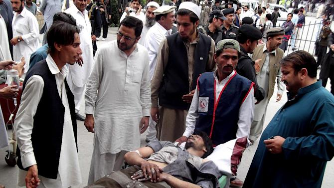 People stand near a man injured from an explosion, at a local hospital in Pakistani tribal area of Parachinar, Monday, May 6, 2013. A bomb blast tore through a political rally held by an Islamist party in northwest Pakistan Monday, killing many people and wounding dozens more as the country's already bloody election race gets even more dangerous ahead of the May 11 vote. (AP Photo/Ali Murtaza)