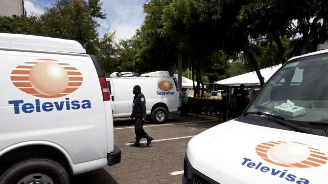 A Nicaraguan National Police officer walks between a confiscated fleet of vans bearing the logo of Mexican news channel Televisa at a presentation of 18 foreigners believed to be Mexican nationals who posed as Televisa journalists, in Managua, Nicaragua, Friday, Aug. 24, 2012. Police Commissioner Aminta Granera said the men posed as journalists to cover the trial of Nicaraguan businessman Henry Farinas, survivor of an attack that killed the singer Facundo Cabral last year. The Mexican ambassador to Nicaragua confirmed that the Mexican news channel has no correspondents in Nicaragua. It is unclear why the men were posing as journalists. (AP Photo/Esteban Felix)