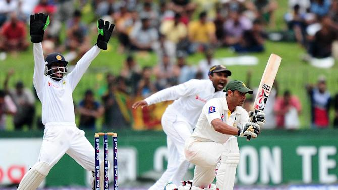 Sri Lanka's Niroshan Dickwella (L) and Mahela Jayawardene (C) successfully appeal for a Leg Before Wicket decision against Pakistan's Abdur Rehman (R) during the fourth day of the second Test in Colombo on August 17, 2014