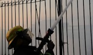 A firefighter extinguishes a fire in Quezon City, east of the Philippine capital of Manila on April 19, 2012. Foreigners are believed to be among six people who died on Friday when a fire razed a small hotel near a former US naval base in the Philippines, rescue officials said