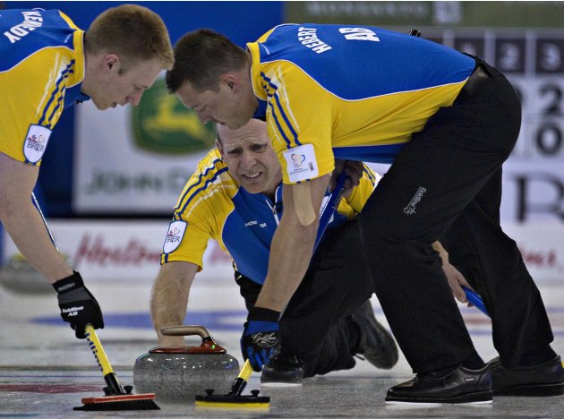 Alberta skip Martin reacts to his shot as teammates Kennedy and Hebert sweep during play at the Canadian Men's Curling Championships in Edmonton
