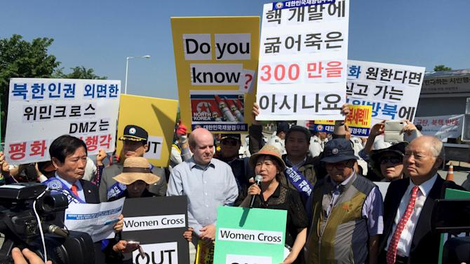 Conservative protesters hold placards during a rally against the WomanCrossDMZ group, who are holding a peace march nearby, near the Demilitarised Zone (DMZ) between North and South Korea