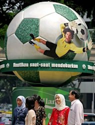 Malaysians walk past an advertisment for the World Cup in downtown Kuala Lumpur in 2006. Gambling on football is illegal in Malaysia. Most other types of gambling also are illegal outside of the country's sole casino resort in the Genting Highlands near the capital Kuala Lumpur